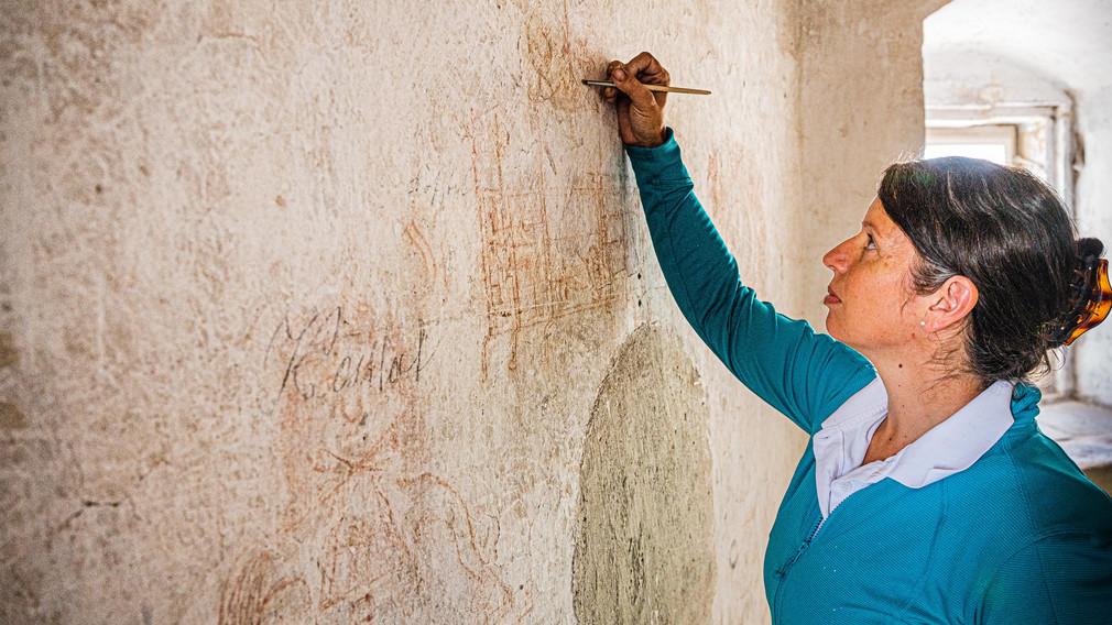 Eine Frau arbeitet an der Freilegung von Wandzeichnungen, welche sie im Zuge von Restaurierungsarbeiten im St. Pöltner Rathausturm entdeckt hat. (Foto: Arman Kalteis)