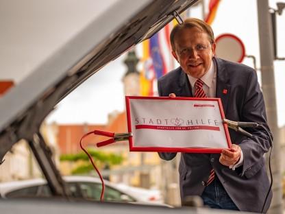 """Bürgermeister Matthias Stadler mit """"Stadthilfe""""-Schild vor einem Auto am Rathausplatz. (Foto: A. Behpournia)"""