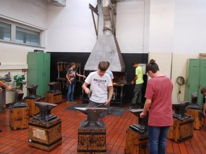 Sieben Jugendliche beim Schmieden in einer Werkstätte. (Foto: HTL St. Pölten).