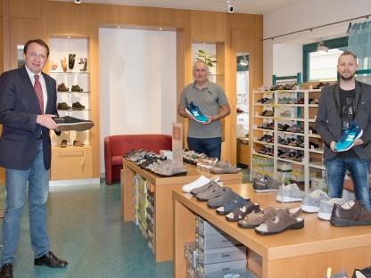 Drei Personen stehen in einem Geschäft und halten Laufschuhe in der Hand. Foto: Josef Vorlaufer