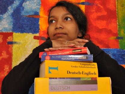 Mädchen lehnt Kopf mit verschränkten Händen auf Bücherstapel. (Foto: Thomas Kainz).