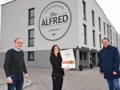 Alex Meder (Betreiber), Martina Thaler (Marketing) und Matthias Stadler stehen vor dem Hotel und zeigen die Frühstücksbox. Foto: Josef Vorlaufer