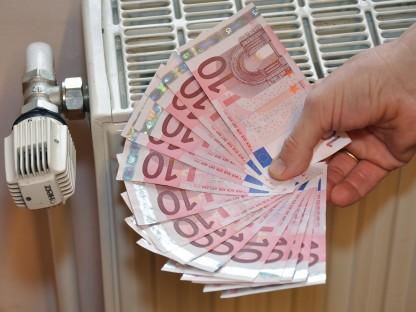 Hand mit Euroscheinen vor Heizkörper. (Foto: Josef Vorlaufer)