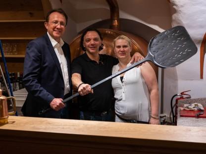 Bürgermeister Mag. Matthias Stadler gratuliert Michele Madonna und seiner Frau zur Eröffnung. Im Bild sind alle drei mit einem großen Pizzaheber zu sehen (Foto: Arman Behpournia).