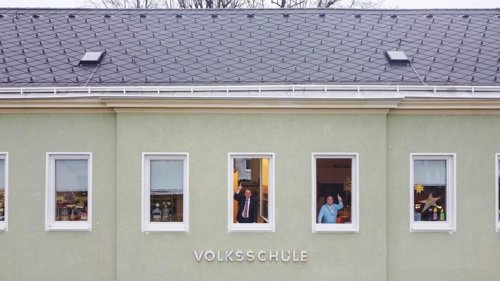 Bürgermeister Matthias Stadler und Schulamtsleiter Andreas Schmidt schauen aus Fenstern des Kindergarten- und Volksschul-Gebäude in Ratzersdorf. und zeigen nach oben in Richtung des Daches.