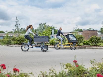 Vater, Mutter und Kind fahren mit einem Lastenrad durch die Stadt.