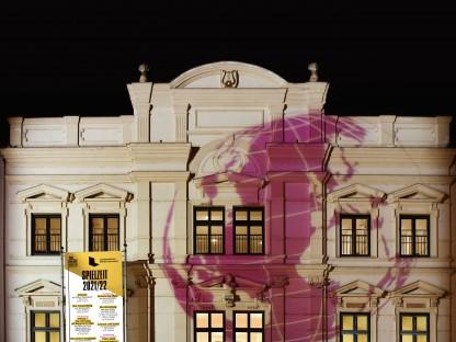 """Das beleuchtete Landestheater Niederösterreich bei Nacht ist zu sehen. Auf die Fassade ist eine violette Weltkugel projiziert und eine Fahne mit der Aufschrift """"Spielzeit 2021"""" sowie einer Auswahl des Programms steht vor dem Gebäude. (Foto: Alexi Pelekanos)"""