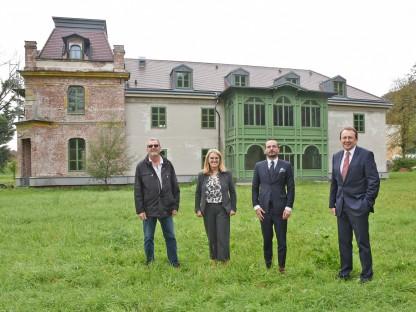 Vier Personen am Standort für das neue PVZ vor dem Herrenhaus in Viehofen. (Foto: Vorlaufer)