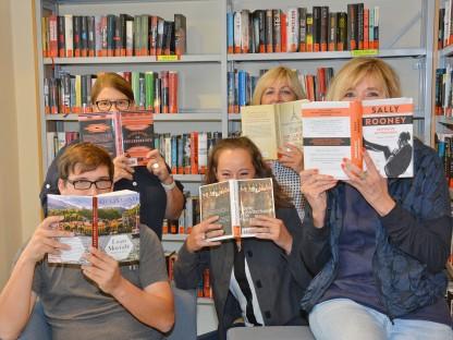 Fünf MitarbeiterInnen der Stadtbücherei verdecken ihren Mund mit Büchern. (Archivbild, Foto Medienservice)