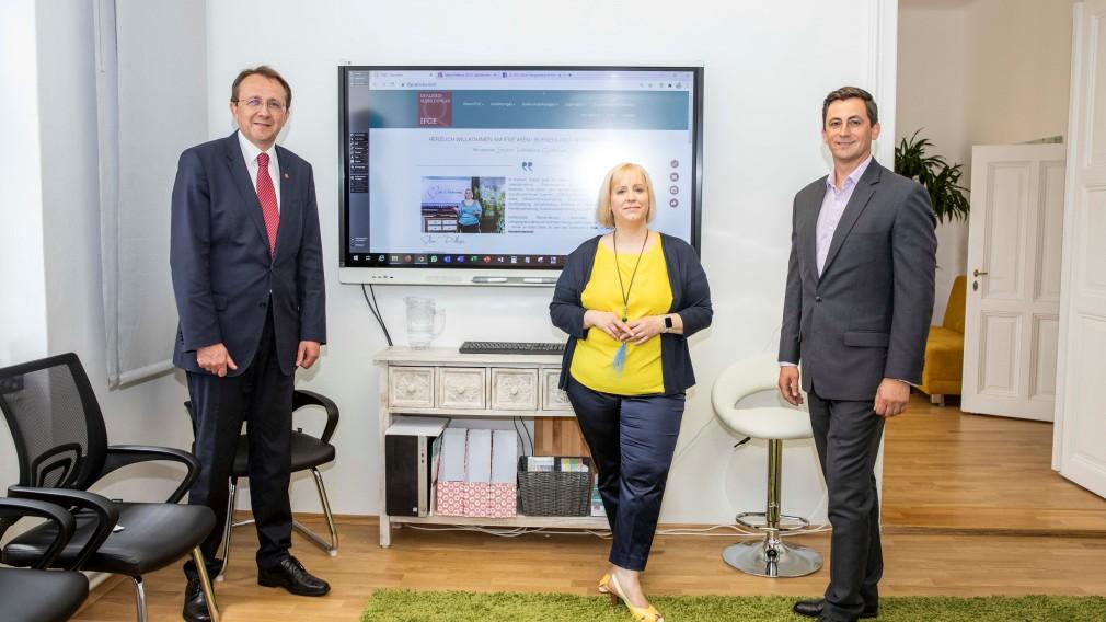 Drei Personen stehen nebeneindander in einem Seminarraum , dahinter ist ein Fernseher auf dem die Homepage des IFGE zu sehen ist.