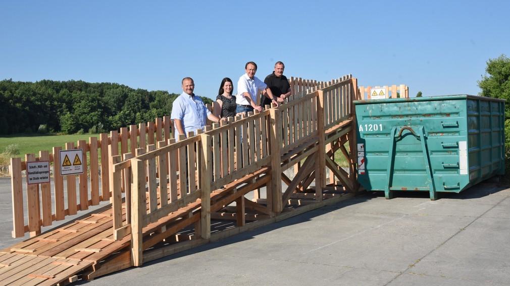 Vier Personen stehen auf einer Rampe zu einem Container.