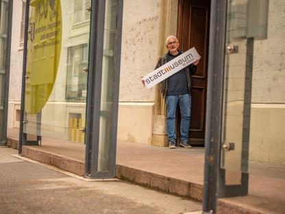 """Mag. Thomas Pulle mit einem Schild mit der Aufschrift """"Stadtmuseum St. Pölten"""" in den Händen vor dem Stadtmuseum St. Pölten. (Foto: Arman Behpournia)"""