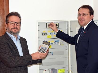 Thomas Zeh (Referatsleiter Technischer Umweltschutz) mit Taschenrechner und Bürgermeister Matthias Stadler stehen vor dem Stromzählerkasten. (Foto: Josef Vorlaufer)