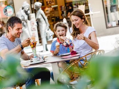Ein Mann, ein Junge und eine Frau sitzen an einem Tisch und essen Eiscreme. (Foto: Doris Schwarz-König)