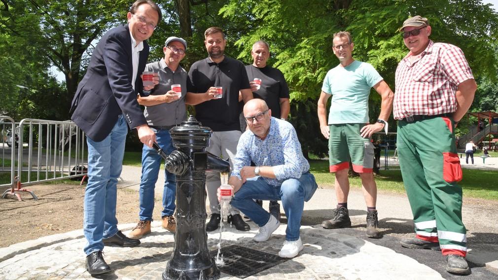 Sieben Personen posieren für ein Foto bei einem Trinkwasserbrunnen. (Foto: Josef Vorlaufer)