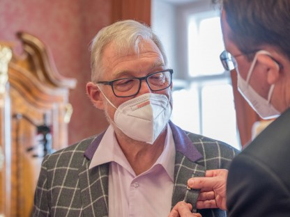 Bürgermeister Matthias Stadler steckt die Nadel mit dem Ehrenzeichen der Stadt St. Pölten an das Jackett von Dr. Harald Mayr an.