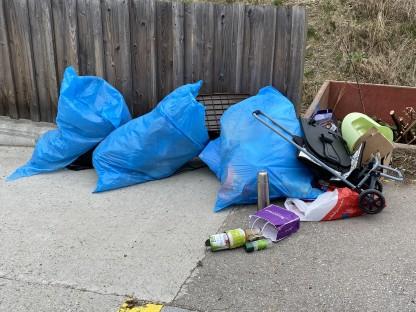 Ein illegal abgelagerter Müllhaufen. Große mit Müll befüllte Plastiksäcke und anderer Sperrmüll liegen auf einem Gehweg.