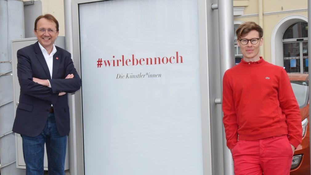 Bürgermeister Matthias Stadler und der Aktionskünstler donhofer. stehen neben einem der Plakate. (Foto Vorlaufer)