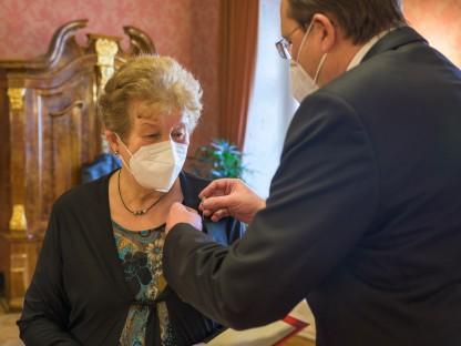 Bürgermeister Matthias Stadler steckt die Nadel mit dem Ehrenzeichen der Stadt St. Pölten an die Weste von Hannelore Mann an.