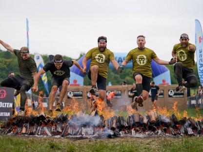 Teilnehmer des Spartan Race beim Sprung über ein brennendes Hindernis. (Foto: Josef Bollwein)
