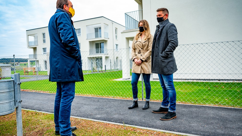 Ein Pärchen und Bürgermeister Matthias Stadler im Gespräch. Im Hintergrund ist der neu errichtete Wohnbau zu sehen, in dem Christopher Fertner und seine Freundin Lisa Wissijak einziehen werden.