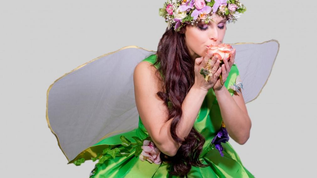 Frau in grünem Kleid mit Blumenschmuck am Kopf und durchsichtigen Flügerl posiert als Blumenfee. (Foto: Tanja Wagner)