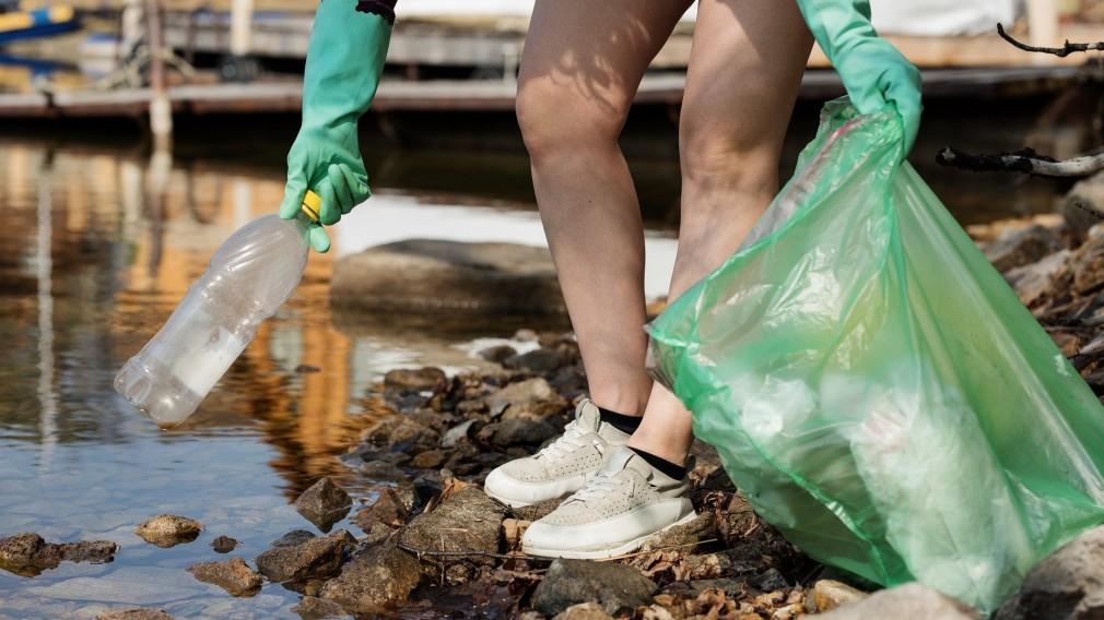 Eine Frau mit Handschuhen und einem Müllsack in der Hand hebt eine Plastikflasche am Ufer eines Flusses auf. (Foto: Pixabay | nastya_gepp)