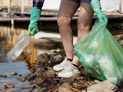 Eine Frau mit Handschuhen und einem Müllsack in der Hand hebt eine Plastikflasche am Ufer eines Flusses auf. (Foto: Pixabay   nastya_gepp)
