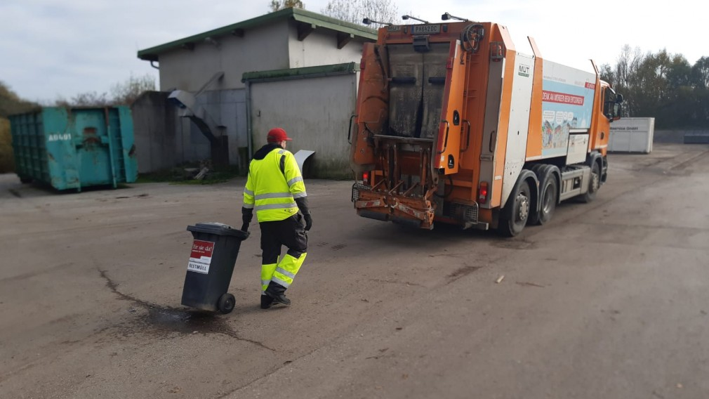 Mitarbeiter der Müllabfuhr bringt Mülltonne zu Müllentsorungs-Lastkraftwagen. (Foto: Jürgen Pomberger)