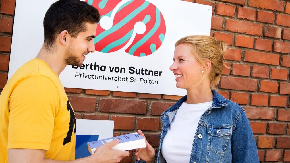Ein Mann der einer Frau ein Buch reicht, vor einer Fassade mit dem Logo der Bertha von Suttner Privatuniversität St. Pölten. (Foto: Christian-Ariel-Heredia)