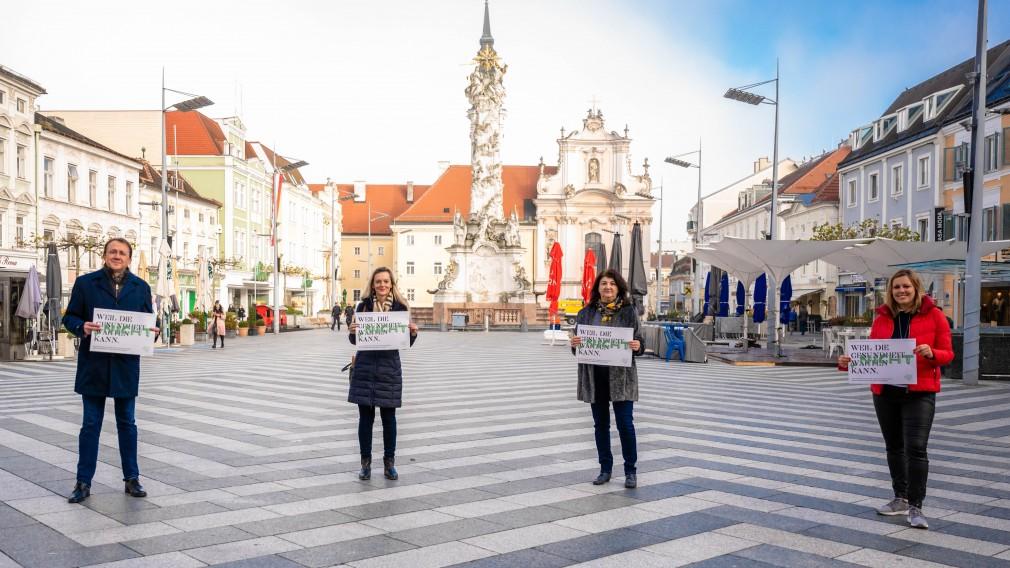 Bürgermeister Matthias Stadler, Claudia Pommer (Psychologin/Psychotherapeutin) , Mirsada Zupani (Sozialarbeiterin und Case Management) und Nihada Kotoucek (Psychotherapeutin) stehen am Rathausplatz mit einem Plakat auf dem steht: Weil die Gesundheit nicht warten kann. Foto: Arman Kalteis