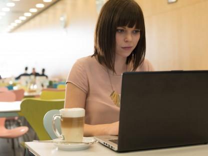 Eine junge Frau in der Mensa der Fachhochschule St. Pölten, sitzend mit einem Laptop. (Foto: Martin Lifka)