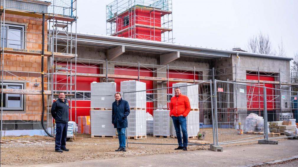 Feuerwehrkommandant Helmut Stadlbauer, Bürgermeister Matthias Stadler und der Geschäftsführer der Immobiliengesellschaft St. Pölten Martin Sadler stehen vor dem neuen Feuerwehrhaus der FF viehofen, das sich noch im Bau befindet.