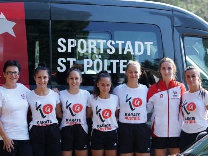 Karathe-Sportlerinnen posieren vor dem Sportbus der Stadt St. Pölten