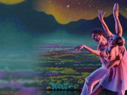 Ein Tänzer und eine Tänzerin führen auf einer Bühne ein Ballettestück vor.