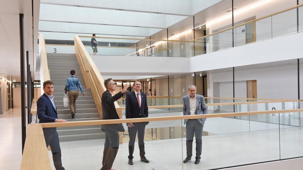 Vier Personen besichtigen den Innenraum des neuen Campus.(Foto: Josef Vorlaufer)