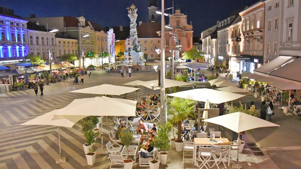Blick vom Rathaus auf den Rathausplatz mit Schanigärten in der Dämmerung (Foto: Josef Vorlaufer).