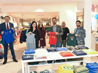 Bürgermeister Matthias Stadler und Vertreter der Stadt sowie die Betreiber des neuen Benetton-Store mit Kleidungsstücken im Geschäftslokal. (Foto: Vorlaufer)