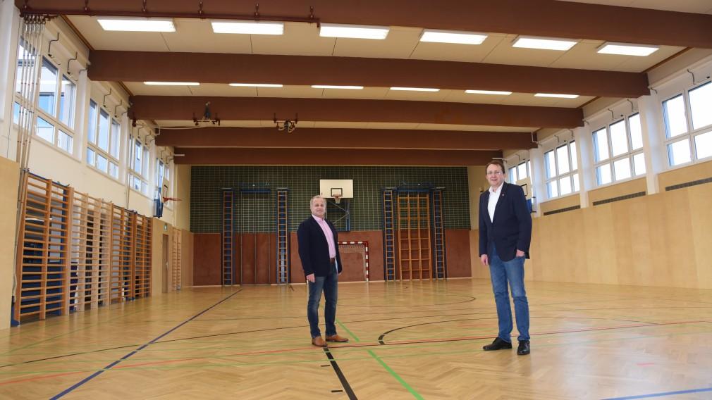 Bürgermeister Matthias Stadler und Schulamtsleiter Andreas Schmidt befinden sich im Turnsaal der MS Pottenbrunn, wo ein neuer Vollholzboden und neue Wandvertäfelungen verlegt wurden.