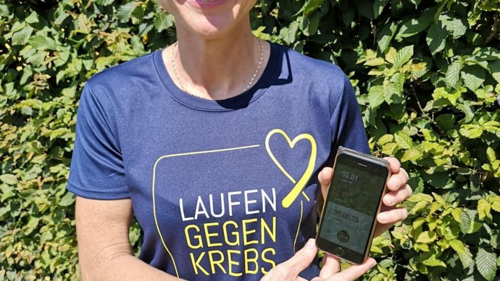 Frau mit Frauenlauf T-Shirt und Smartphone in der Hand. (Foto: Frauenlauf)