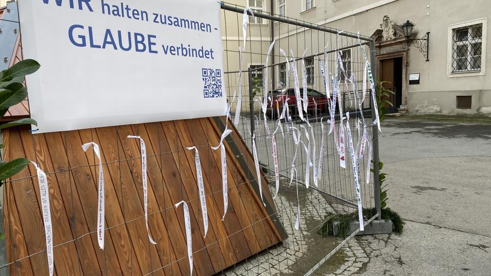 Weiße Bänder mit Friedensbotschaften hängen an einem Bauzaun. Foto: Diözese St. Pölten