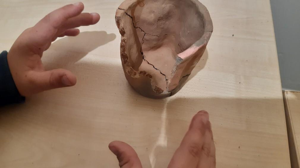Kinderhände und ein Keramikgefäß mit Rissen. (Foto: Stadtmuseum).