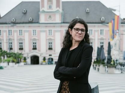 Angelika Schopper an einem Stein lehnend vor dem Rathaus