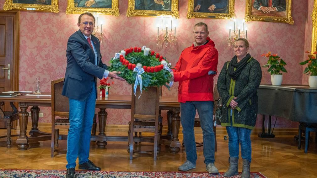Pfarrer David Zezula und Diakoniebeauftragte Marion Posch bei der Übergabe des evangelischen Adventkranzes mit 24 Kerzen an Bürgermeister Matthias Stadler (Foto: Arman Kalteis)